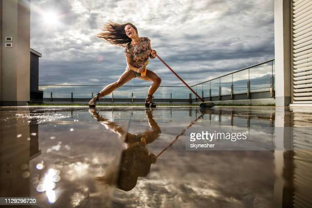 young sensual woman having fun while mopping wet floor on penthouse terrace. - scope foto e immagini stock