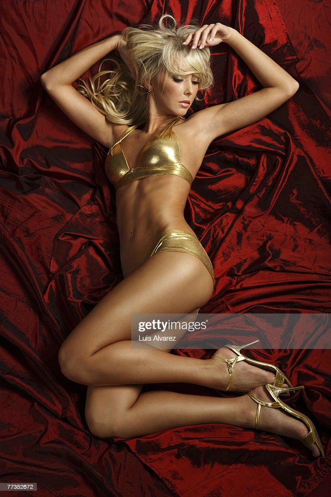 Young sensual woman in gold lingerie on red bed : Photo