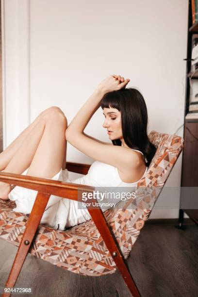 young sensual woman sitting on chair - human leg stock photos and pictures