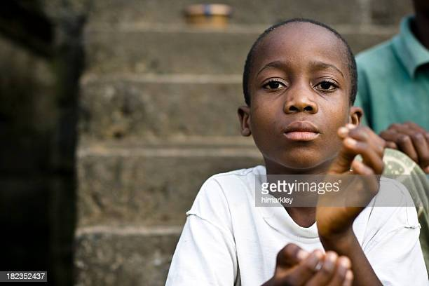 Young serious boy with hands in the air