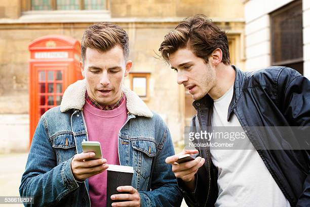 Young serious British men discussing news on mobile phone outdoors