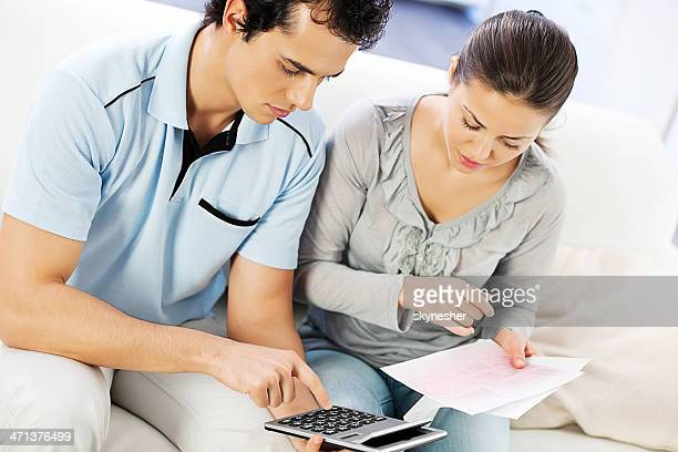 Young serious couple doing their taxes.