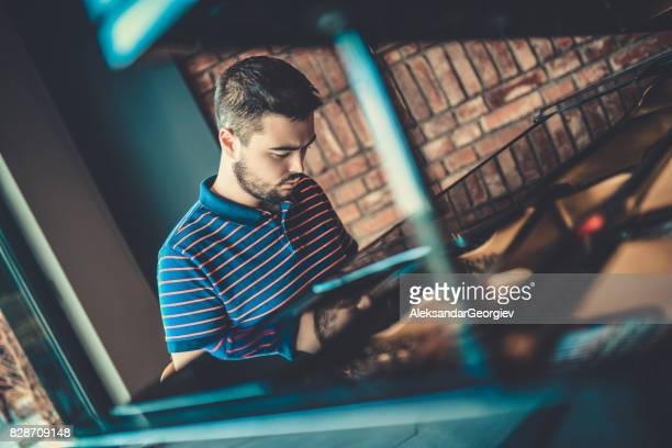 Young Serious Musician Playing Piano in Modern Jazz Club