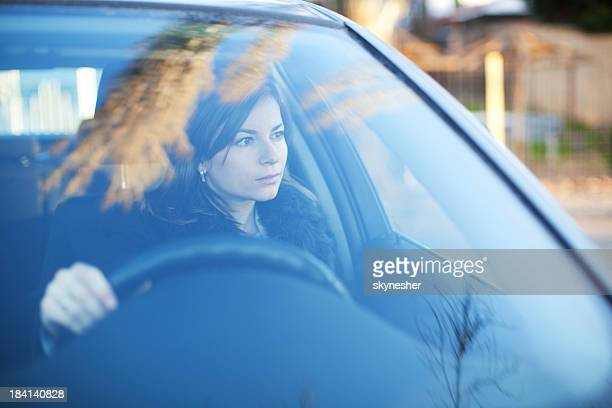 Young serious woman is driving a car