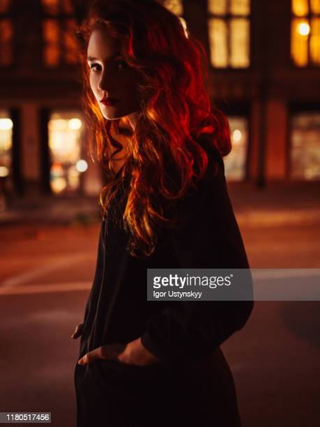 young serious woman outside building at night - coat stock pictures, royalty-free photos & images