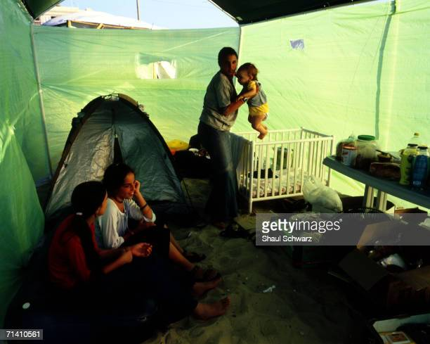 A young settler picks up a baby inside a tent in the newly built tent city July 16 2005 in the beach settlement of Shirat Hayam Gaza Strip This tent...