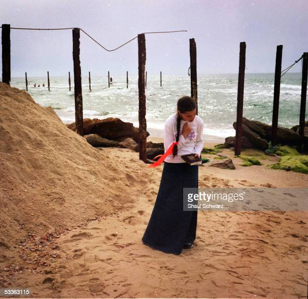 A young settler woman prays near the beach June 15 2005 in Gush Katif Gaza Strip With the pullout plan time table ticking the 9000 Jewish settlers of...