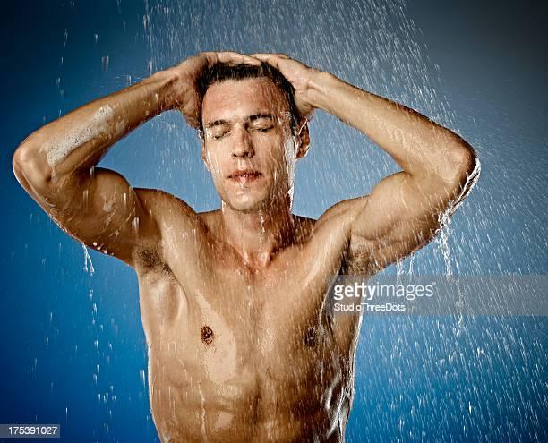 sexy joven hombre tener una ducha - hombre duchandose fotografías e imágenes de stock