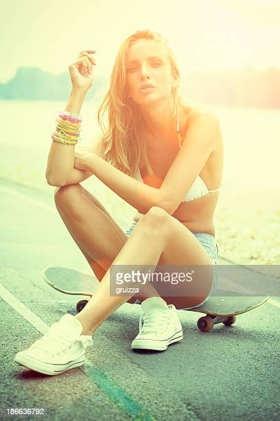 Young sexy skater girl in jeans sitting on her skateboard