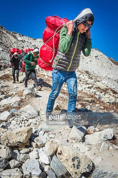 探検機器の登山道ヒマラヤネパールを運ぶ若いシェルパポーター - 職業 ポーター ストックフォトと画像