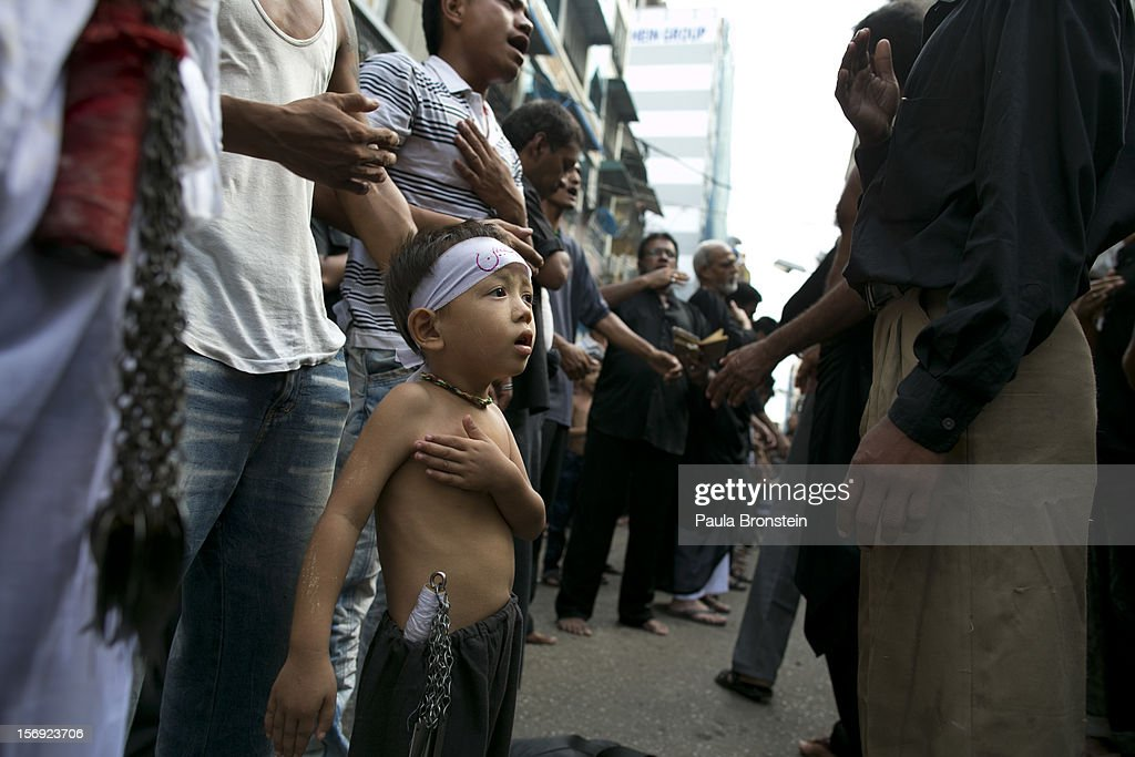 A young Shia muslim boy pounds his chest alongside his father as they mark the day of Ashura on November 25, 2012 in Yangon, Myanmar. The day of Ashura is a national holiday held on the 10th day of Muharram in the Islamic calendar, with men beating themselves as they mourn the martyrdom of Husayn ibn Ali, the grandson of the Islamic Prophet Muhammad. There are approximately 20,000 Shia muslims in Myanmar.