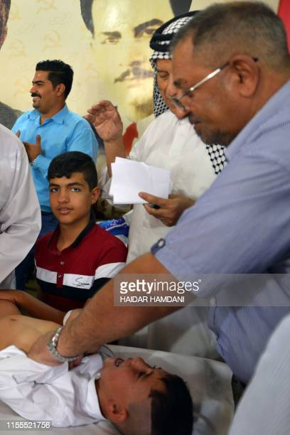 Young Shiite Muslim boy reacts as he's being circumcised by a doctor in the Iraqi holy central city of Najaf on July 14, 2019. - In Islam...