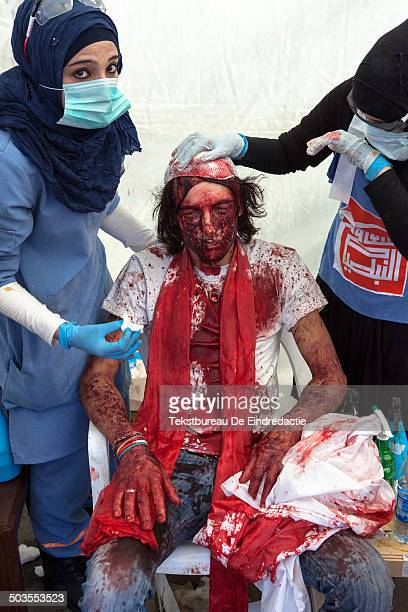 CONTENT] A young Shi'ite Muslim man covered in his own blood with a selfinflicted head wound receiving medical assistance by female nurses in a...