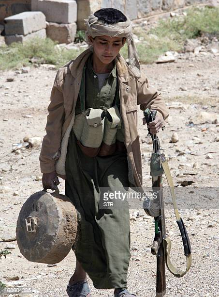 A young Shiite Yemeni Huthi militant collects unexploded landmines in a destroyed area in Harf Sufyan in Yemen's Amran province 70 kms north of Sanaa...