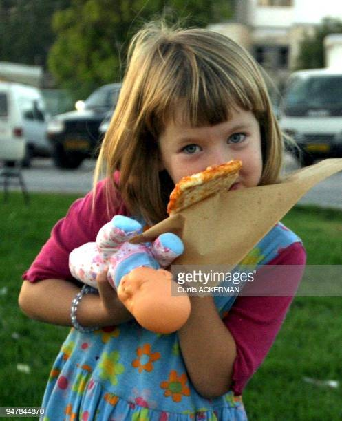 A young Shilo settler girl enjoys a slice of pizza during a community event Shilo is a large West Bank settlement located north of Jerusalem was once...