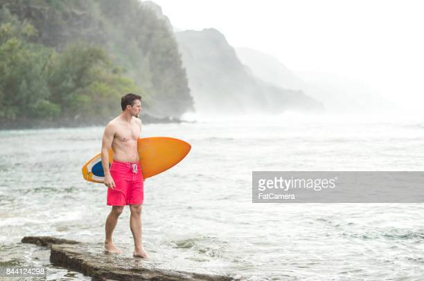 young shirtless man with surfboard on hawaii beach - fatcamera stock pictures, royalty-free photos & images
