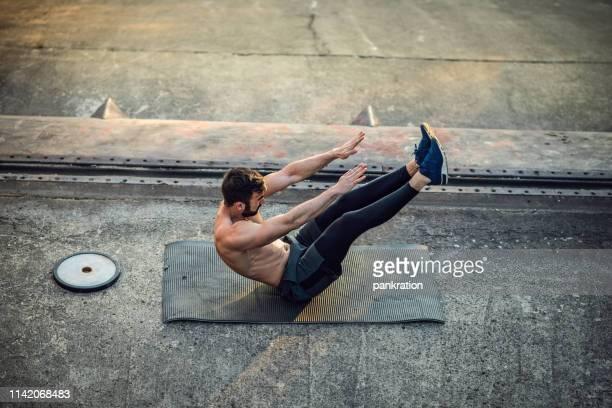 日没で屋外の重みを持つ若い上半身裸筋肉男の訓練 - 自重トレーニング ストックフォトと画像