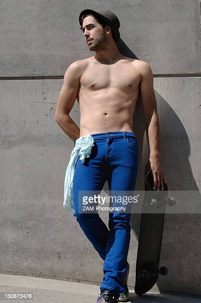Young shirtless skater in front of a concrete wall