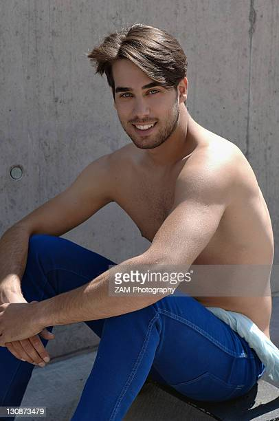 Young shirtless skater in front of a concrete wall, sitting on his skateboard