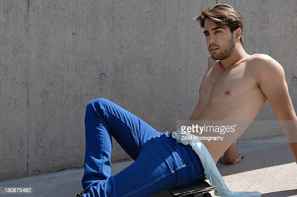 young shirtless skater in front of a concrete wall, sitting on his skateboard - ragazzi fighi nudi foto e immagini stock