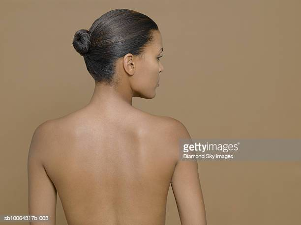 Young shirtless woman, rear view