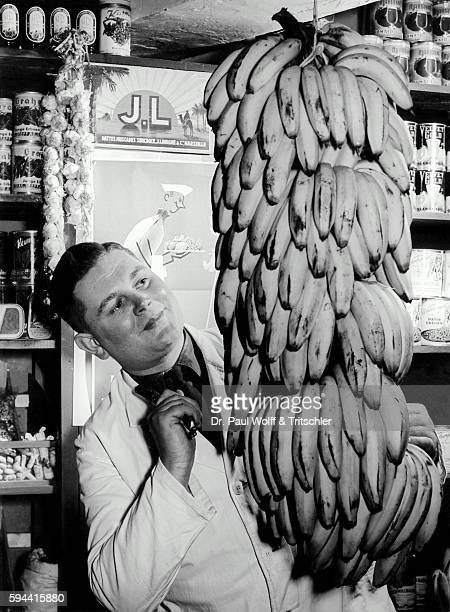 Young shop assistant looking at bananas in a supermarket nostalgia