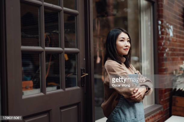 young shop owner with arm crossed standing in front of her retail store - planning stock pictures, royalty-free photos & images