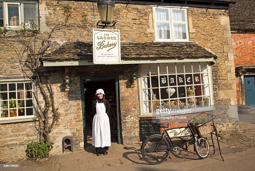 Young Shopkeeper Woman In Old Fashioned Traditional Clothing Outside The Village Bakery Shop Lacock