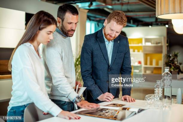 a young shopper couple browsing the catalogue booklet lying on a table with a sales rep in a home diy store - interior design foto e immagini stock