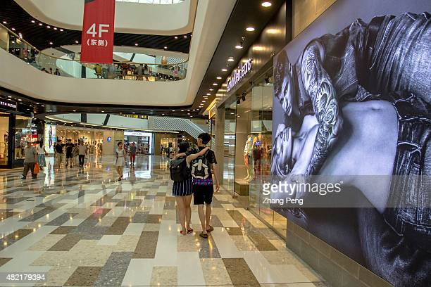 Young shoppers walk past a huge fashion billboard in Tongzhou Wanda department store newly opened in the end of 2014 Dalian Wanda Group Co Chinese...
