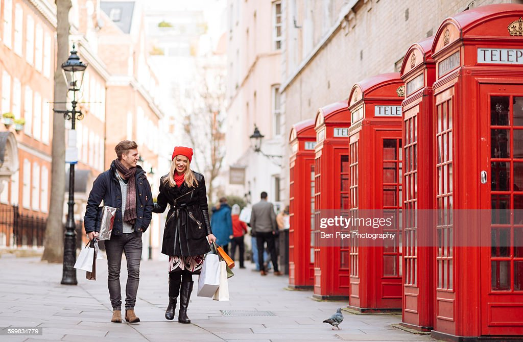 Young shopping couple strolling past red phone boxes, London, UK : Stock Photo