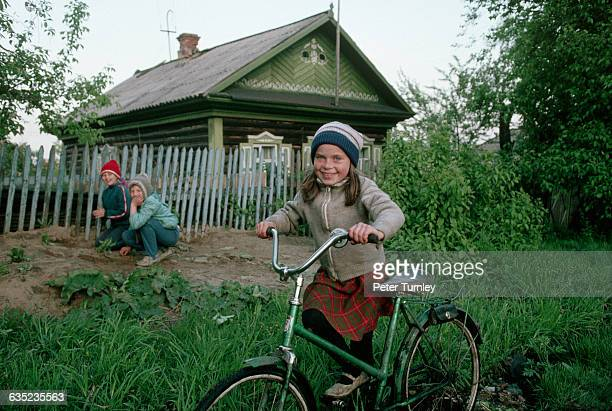 A young Siberian girl pushes her bicycle through the grass She lives in a poor coalmining and steelmanufacturing town enduring widespread economic...