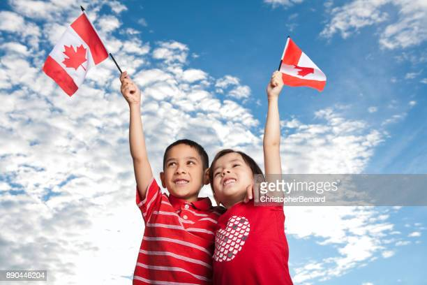 young sibling celebrating canada day - canada day stock pictures, royalty-free photos & images