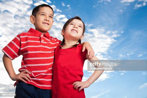 Young sibling hugging against sky