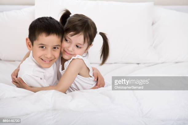 Young sibling hugging in bed
