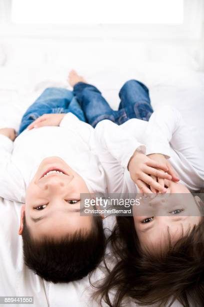Young sibling laughing in bed