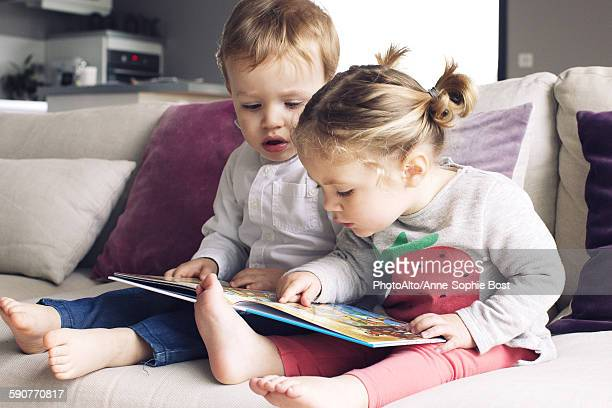Young siblings looking at book together