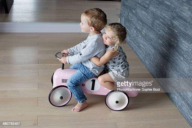 Young siblings riding on toy car together