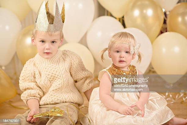 Young siblings with gold balloons
