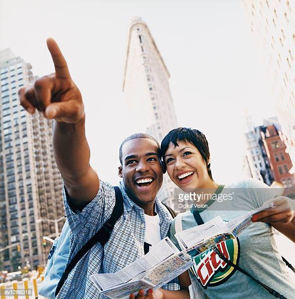 Young Sightseeing Couple in New York Pointing and Standing in Front of the Flatiron Building