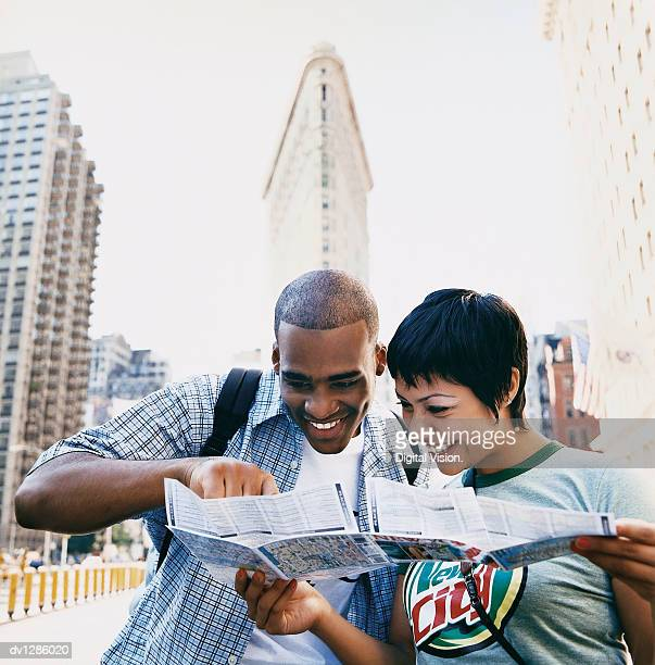 Young Sightseeing Couple in New York Standing in Front of the Flatiron Building Examining a Map