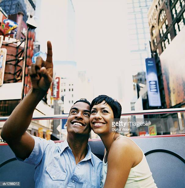young sightseeing couple travelling on an open top bus in new york city - double decker bus stock pictures, royalty-free photos & images
