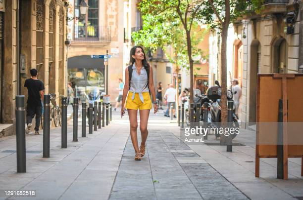 young sightseer enjoying barcelona side street in summer - approaching stock pictures, royalty-free photos & images