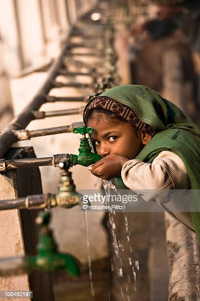 Young sikh girl drinks water from  communal taps