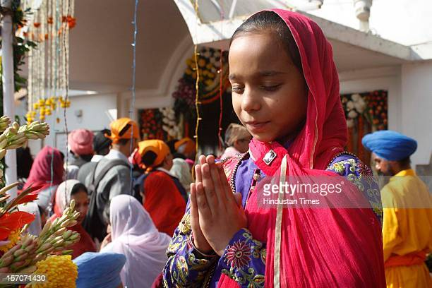 Young sikh girl offer prayers at Gurdwara on the occasion of 543rd anniversary of the founder of Sikh religion Guru Nanak at Sector 18 on November...