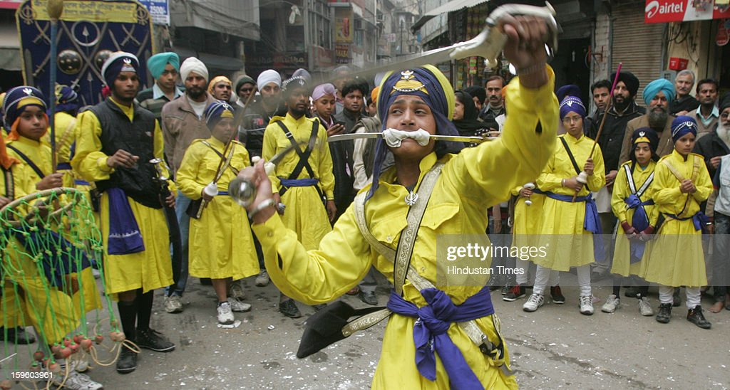 A young Sikh warrior playing with three swords as showing their traditional Sikh Marshal Art skills while taking part in the religious procession on the eve of Birth Anniversary of 10th Sikh Guru Gobind Singh Ji, on January 17, 2013 in Amritsar, India. Guru Gobind Singh Ji was 10th and the last of the living Sikh Gurus who founded the Sikh Khalsa in 1699.
