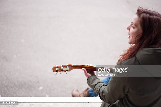 Young singer songwriter singing outdoors