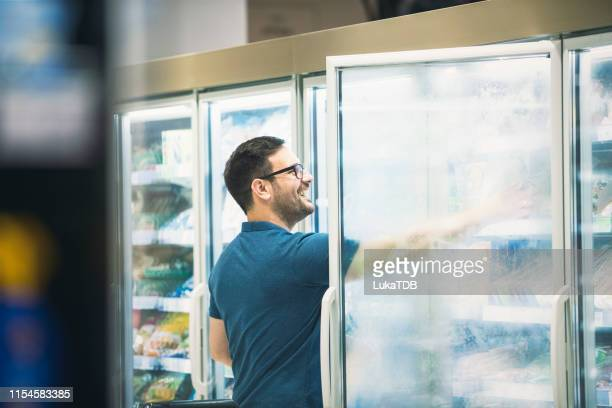 young single man buying groceries at the supermarket - convenience store stock pictures, royalty-free photos & images