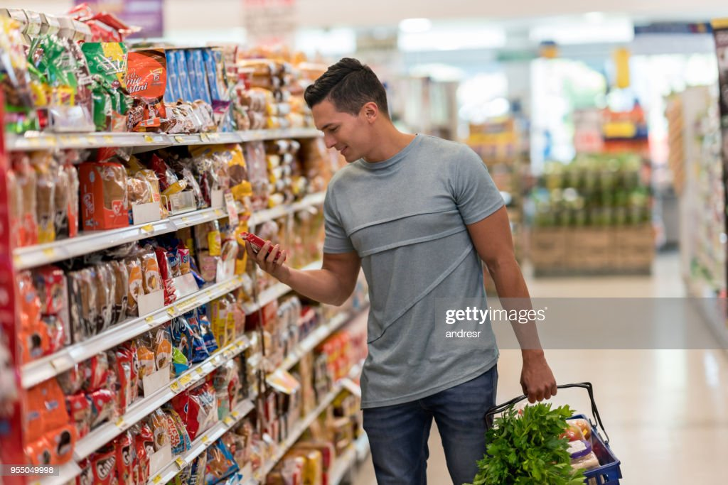 Young single man buying groceries at the supermarket reading the label of a product looking very happy : Stock Photo