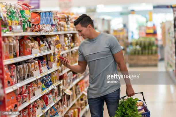 Young single man buying groceries at the supermarket reading the label of a product looking very happy